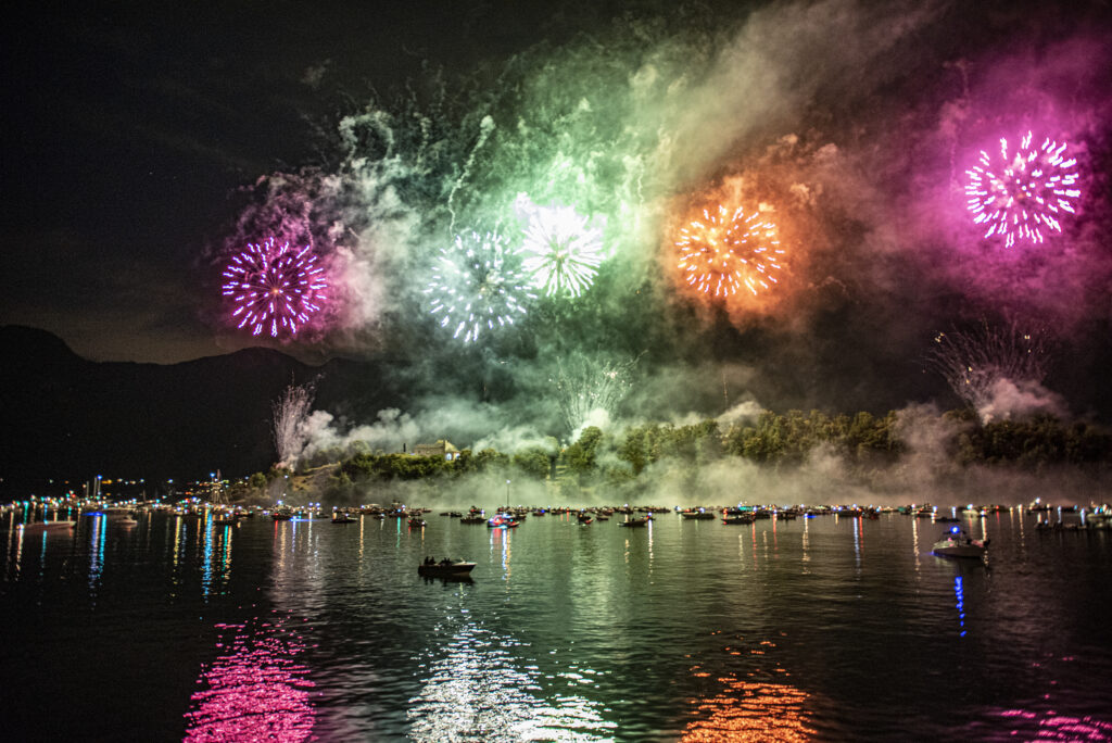 Fireworks over Lake Como. The fireworks reflect on the water. Small boats in the distance.