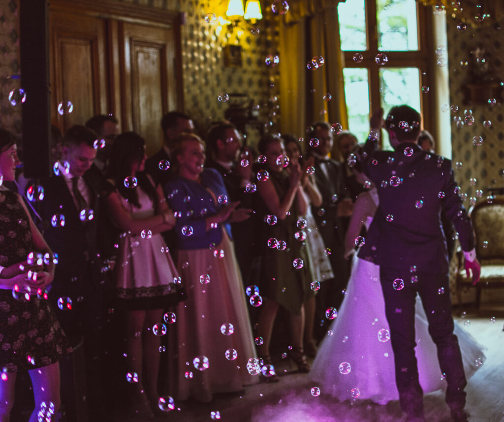 Photo of a crowd at a wedding. Bride is dancing. Bubbles fill the air. The lighting is purple.