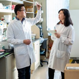 """Shot of two scientists in the lab with white lab coats. Allison Bien (right) with Rao Lab mentor Chan Wang """"Jerry"""" Lio, Ph.D."""